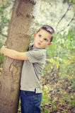 Boy Hugging Tree Stock Image