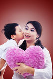 Boy kiss mother holding heart pillow on red Royalty Free Stock Image