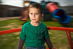 Boy on merry go round Stock Images