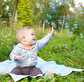 Boy sitting on grass playing with soap bubbles Stock Images