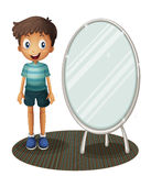 A boy standing beside the mirror Stock Photo