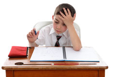 Boy thinkinhg at school desk Royalty Free Stock Image