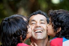 Boys kissing their father Royalty Free Stock Images
