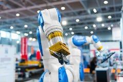 Bras de robot dans une usine Photos stock