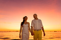 Bride and groom having fun on a tropical beach with the sunset i Royalty Free Stock Photos