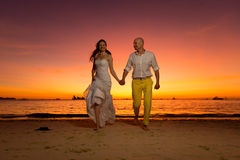 Bride and groom having fun on a tropical beach with the sunset i Stock Images