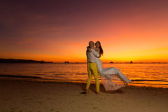 Bride and groom having fun on a tropical beach with the sunset i Royalty Free Stock Photo
