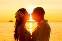Bride and groom kissing on a tropical beach at sunset Stock Photos