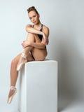 Bruin-eyed de ballerina stellende zitting van Nice op kubus Stock Foto's