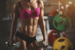 Brutal athletic woman pumping up muscles with Stock Images