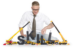 Developing skills: Businessman building skill-word. Royalty Free Stock Images