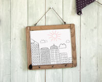 Buildings doodles message board hanging on retro green wooden wa Stock Photos