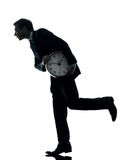 Business man holding clock robbing time  silhouette Royalty Free Stock Image