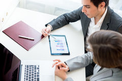Business people analysing a business graph on a tablet computer Stock Photo