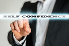 Businessman activating a Self confidence button on virtual scree Royalty Free Stock Photo