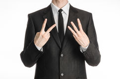 Businessman and gesture topic: a man in a black suit with a tie showing a sign with his right hand two or three left hand sign iso Stock Photo