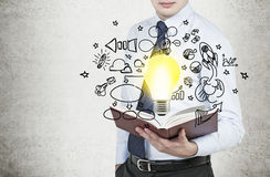 Businessman is holding a book with flying around business icons and a light bulb as a concept of the new business ideas. Stock Images