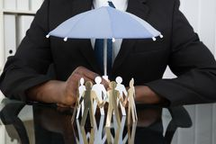 Businessman Holding Umbrella Over Paper Cutout People Stock Photography