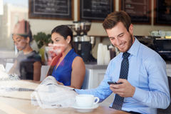 Businessman With Mobile Phone And Newspaper In Coffee Shop Stock Images