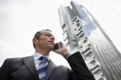 Businessman Using Mobile Phone Against Tall Building Stock Photo