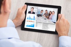 Businessman video conferencing with team on digital tablet Royalty Free Stock Images