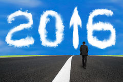 Businessman walking on asphalt road with 2016 arrow sign clouds Stock Photography