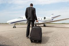 Businessman Walking Towards Corporate Jet Stock Images