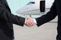 Businessmen handshake in front of a corporate jet Royalty Free Stock Photography