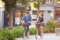 Businesswoman And Businessman Riding Bike Through City Park Royalty Free Stock Photo