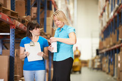 Businesswoman And Female Worker In Distribution Warehouse Stock Photo