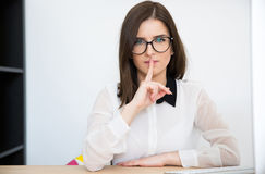 businesswoman sitting at the table with finger over lips Stock Photo