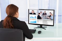 Businesswoman video conferencing with team on computer Stock Photos