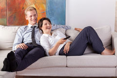 Busy couple watching tv after work Royalty Free Stock Image