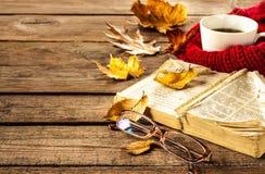 Caffè, libro, vetri e foglie di autunno caldi su fondo di legno Fotografie Stock Libere da Diritti