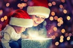 Caixa de presente mágica do Natal e uma mãe e um bebê felizes da família Fotos de Stock