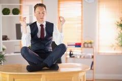 Calm businessman meditating in lotus pose Royalty Free Stock Image