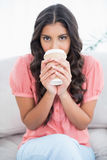 Calm cute brunette sitting on couch drinking from disposable cup Royalty Free Stock Images