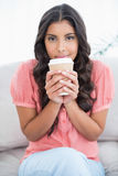 Calm cute brunette sitting on couch holding disposable cup Royalty Free Stock Images