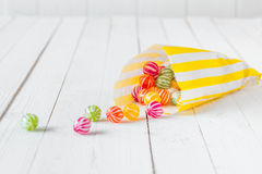 Candy bag spilling the candies over a white table Stock Photo