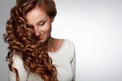 Capelli rossi. Donna con bei capelli ricci Immagini Stock