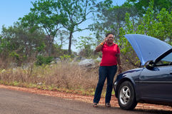 Car breakdown - African American woman call for help, road assistance. Royalty Free Stock Image