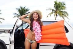 Car rental: happy woman and her car near the beach Royalty Free Stock Photos