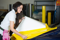 Car wrapper preparing foil to wrap a vehicle Stock Images