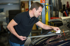 Car wrapper straightening foil with a squeegee Royalty Free Stock Photo
