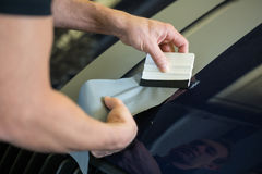 Car wrapper straightening foil with a squeegee Royalty Free Stock Photography