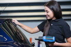 Car wrapper using heat gun and squegee for tinting window Royalty Free Stock Image
