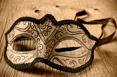 Carnival mask on a wooden surface in sepia toning Royalty Free Stock Image