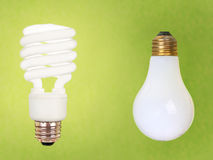 CFL and regular bulbs on green Royalty Free Stock Photo