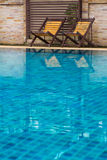 Chair on ground beside swimming pool Royalty Free Stock Photo
