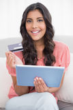 Cheerful cute brunette sitting on couch holding credit card and tablet Stock Photography